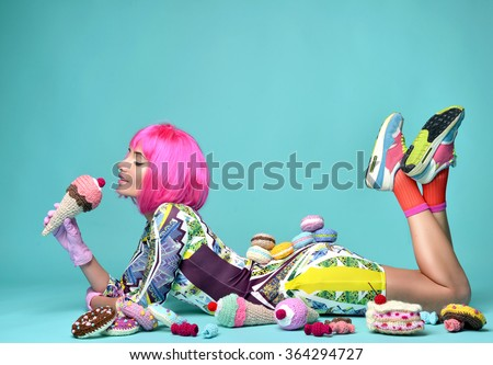 Beautiful funky fashion cheerful woman in hot pink party wig eating fake ice cream and sweet candy cakes candies on a mint background - stock photo