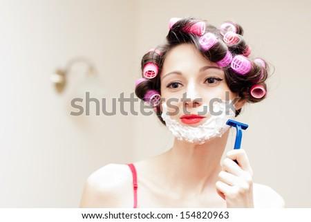 Beautiful funny girl shaving with foam & razor her face - stock photo