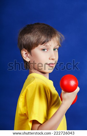 Beautiful funny little child holding a red dumbbell. Sports concept.  - stock photo