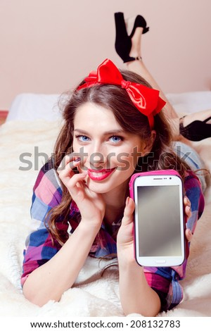 beautiful funny sexy pinup girl relaxing lying in bed showing mobile phone display happy smiling & looking at camera on light copy space background, closeup portrait - stock photo