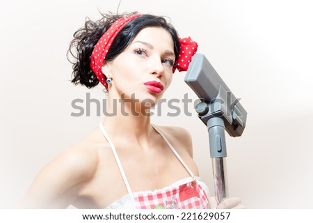 beautiful funny young black haired blue eyes pinup woman with vacuum cleaner - stock photo