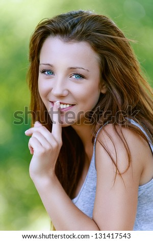 Beautiful funny young woman close-up puts finger to her lips, against background of summer green park. - stock photo
