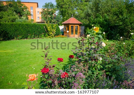 Beautiful garden with blooming roses and a small gazebo - stock photo