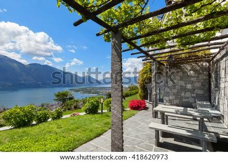 beautiful garden with pergola of a villa, lake view - stock photo