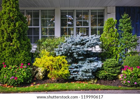 Beautiful garden with trees and flowers in front of windows at home - stock photo
