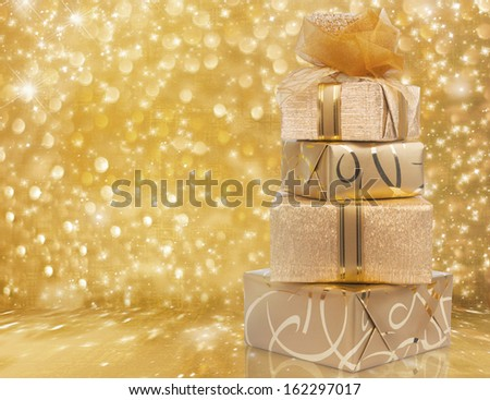 Beautiful gift boxes in gold paper with a silk rose on abstract background - stock photo