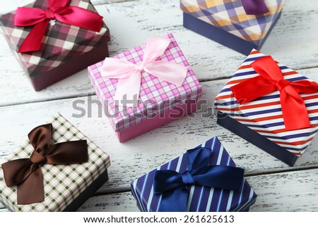 Beautiful gift boxes on white wooden background - stock photo