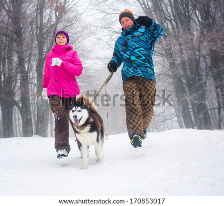 Beautiful girl and boy walking with husky dog in winter forest - stock photo