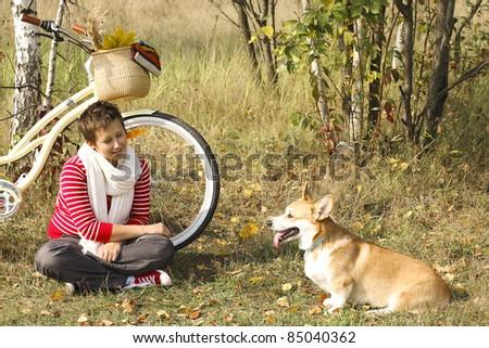 Beautiful girl and corgi dog relaxing near the bike - stock photo