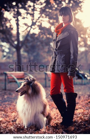 Beautiful girl and her dog in the park  - stock photo