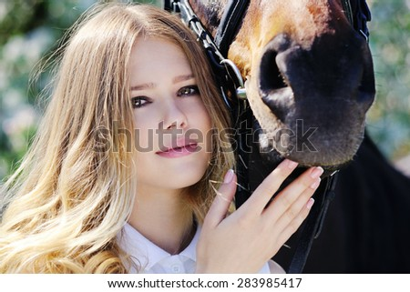 Beautiful girl and horse in spring  - stock photo