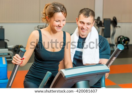 beautiful girl and personal trainer at the gym - stock photo