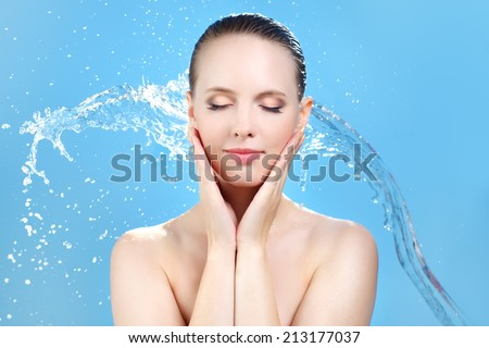 Beautiful girl and stream of water on blue background - stock photo