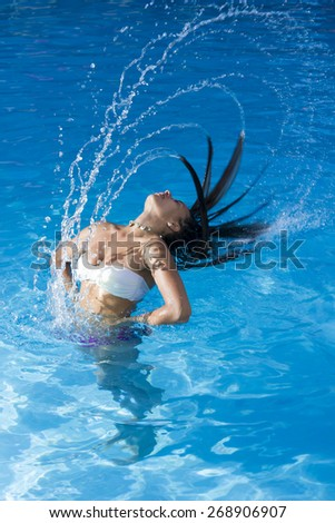 Beautiful girl and water splashes in the swimming pool. - stock photo
