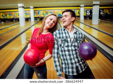 Beautiful girl and young man at the bowling alley with the ball