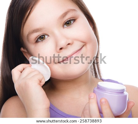 Beautiful girl applying moisturizer cosmetic cream on face, isolated over white - stock photo