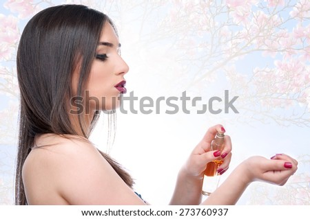 Beautiful girl applying perfume on her hand with magnolia flowers in the background - stock photo