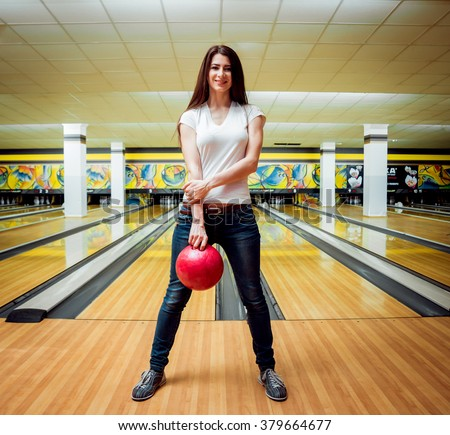 Beautiful girl at the bowling alley with the ball - stock photo
