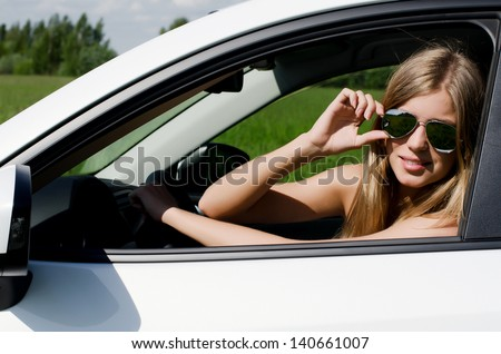 Beautiful girl at wheel the white car - stock photo