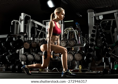 beautiful girl bodybuilder ,  execute exercise with  dumbbells, in dark gym - stock photo
