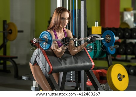 beautiful girl bodybuilder, execute exercise with weight, in green gym - stock photo