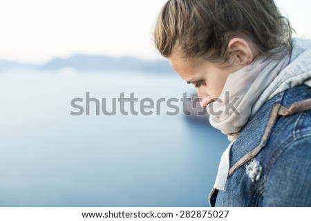 beautiful girl bowed her head sadly. Against the background of the sea landscape - stock photo