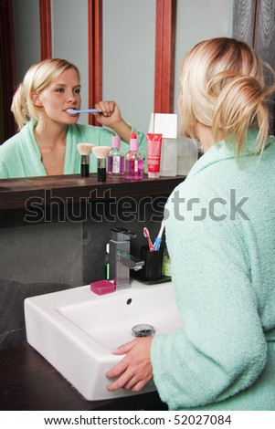beautiful girl brushing her teeth - stock photo