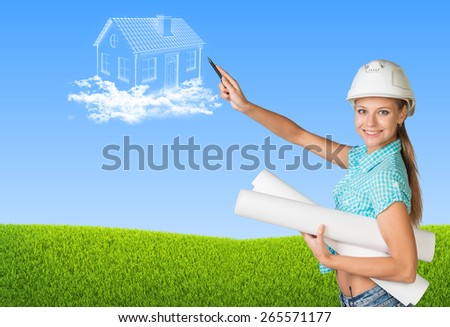 Beautiful girl builder in helmet holding paper scrolls and points to house in clouds. Green field and sky as backdrop - stock photo