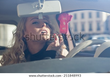 beautiful girl checking her eyes make up in her car - stock photo