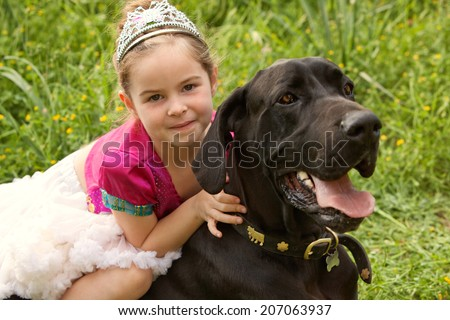 Beautiful girl child and her labrador pet dog hugging while girl sits on the animal back, enjoying a summer holiday in a green grass field wearing a fancy dress. Fun activities and children lifestyle. - stock photo