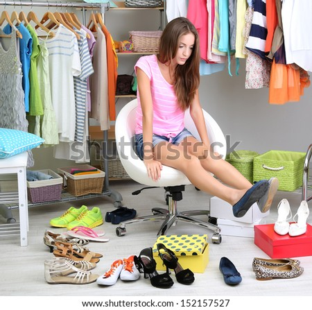 Beautiful girl chooses shoes in room  - stock photo