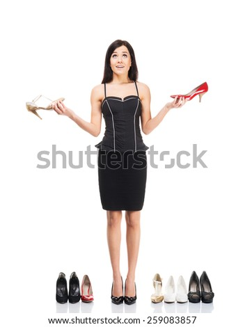 Beautiful girl choosing footwear over grey background - stock photo