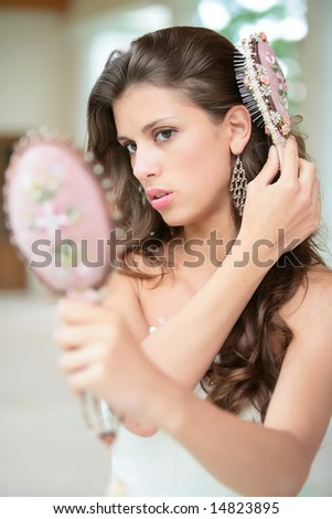 beautiful girl combs luxurious dark hairs, does hairstyle - stock photo