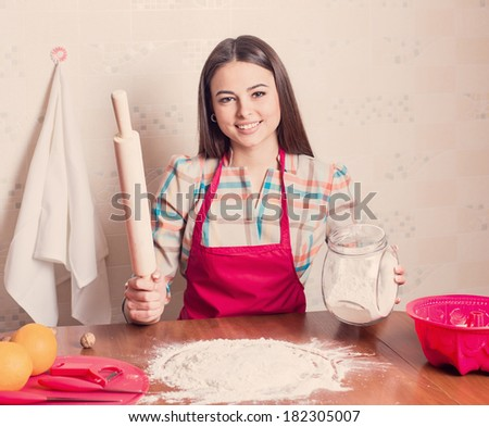 beautiful girl cooking cake in kitchen - stock photo