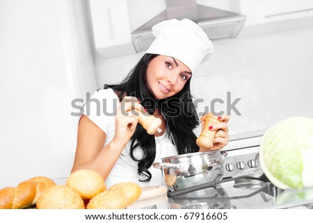beautiful girl cooking in the kitchen at home and adding salt and pepper - stock photo