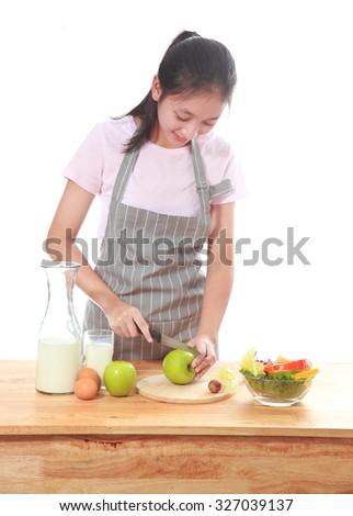 Beautiful girl cooking salad isolated on white background.Little asian girl with vegetables food on white.Beauty girl preparing healthy food at kitchen. - stock photo