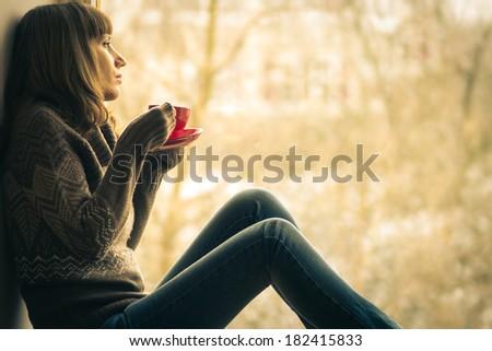 Beautiful girl dreaming with cup of coffee or tea near window - stock photo