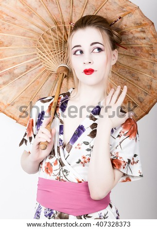 beautiful girl dressed as a geisha girl holding a Chinese umbrella. Geisha makeup and hair dressed in a kimono. The concept of traditional Japanese values - stock photo