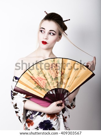 beautiful girl dressed as a geisha, she holds a chinese fan. Geisha makeup and hair dressed in a kimono. The concept of traditional Japanese values. - stock photo