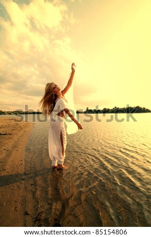 Beautiful girl dressed in arab costume dancing on the beach in the sunset - stock photo