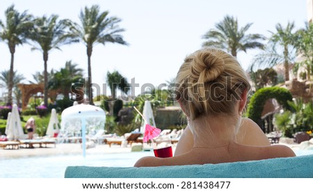 Beautiful girl drinking a cocktail on the beach.  - stock photo