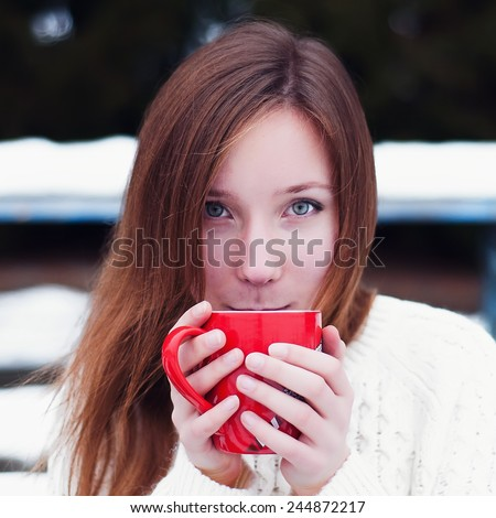 Beautiful girl drinking hot coffee in winter park  - stock photo