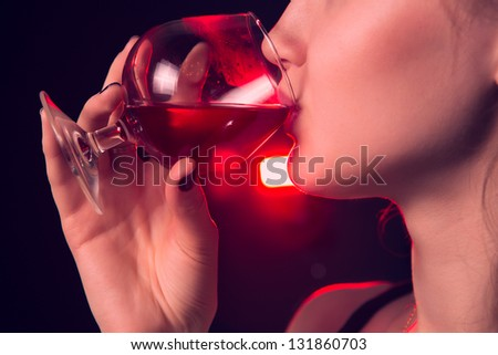 Beautiful girl drinking red wine on black background - stock photo