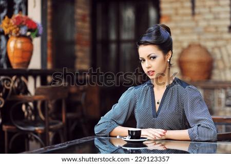 Beautiful girl drinking tea or coffee in cafe - stock photo