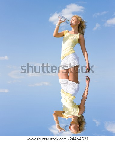 Beautiful girl drinking water against blue sky 2 - stock photo