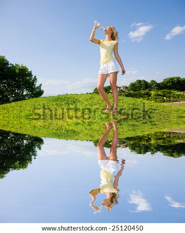 Beautiful girl drinking water against blue sky - stock photo