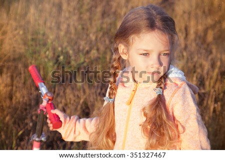 Beautiful girl driving scooter on rural road outdoor in nature - stock photo