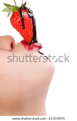 Beautiful girl eating a fresh red strawberry with chocolate sauce - stock photo