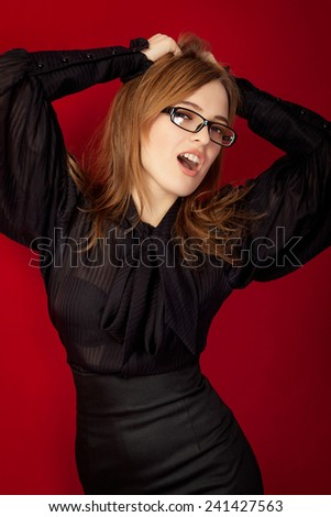 Beautiful girl emotion screaming. Bespectacled sensual girl on a red background. - stock photo