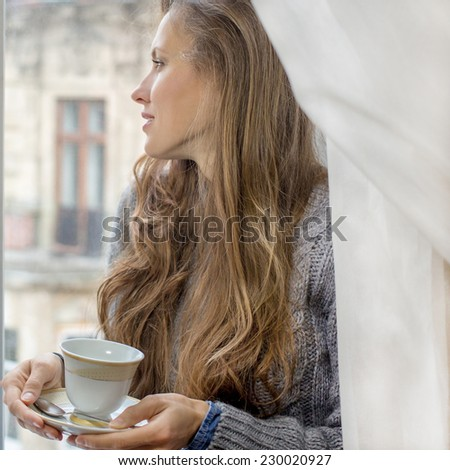 beautiful girl enjoying the freshness of the new day, drinking morning tea of coffee by the window - stock photo